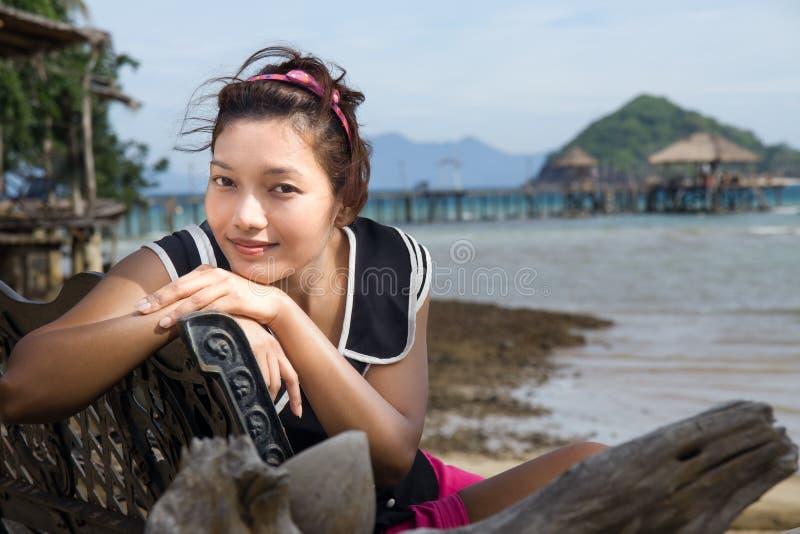Femme s'asseyant sur un banc photographie stock libre de droits