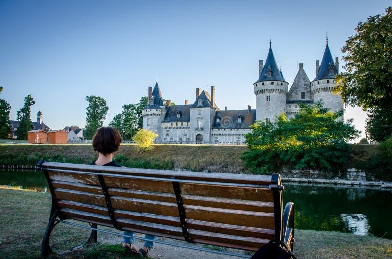 Femme s'asseyant sur un banc contemplant le château du sur la Loire Sully images libres de droits