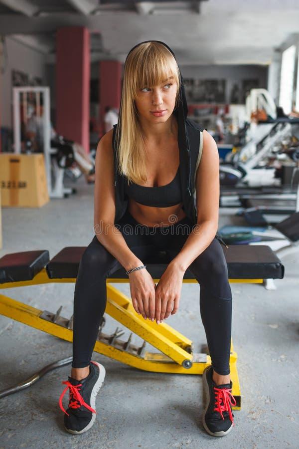 Femme s'asseyant sur un banc dans le gymnase photos stock