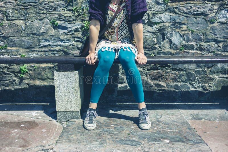 Femme s'asseyant sur un banc dehors images stock