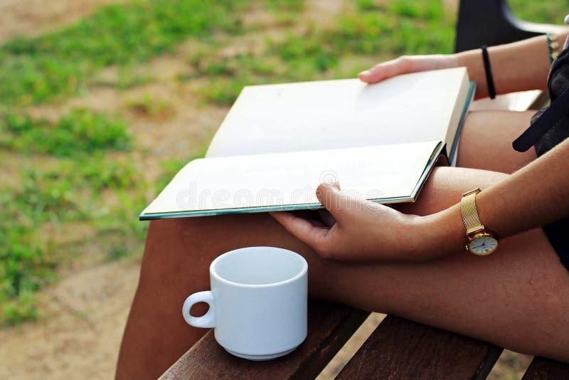 Femme s'asseyant sur un banc lisant un livre dans les bois et buvant une tasse de café images stock