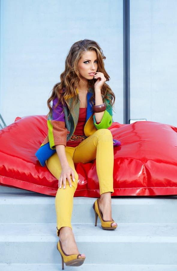 Femme s'asseyant sur un coussin rouge images stock