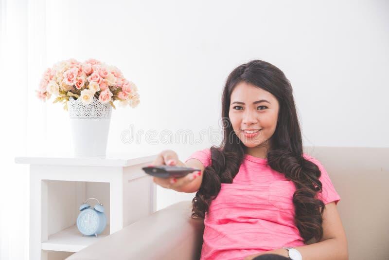 Femme s'asseyant sur un divan, utilisant à télécommande images stock