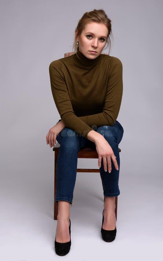 Femme s'asseyant sur une chaise photographie stock