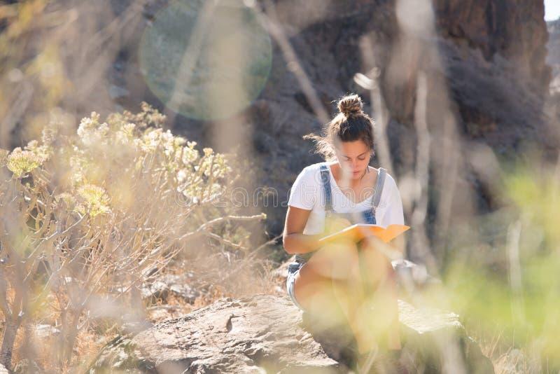 Femme s'asseyant sur une lecture de roche dans les montagnes photos libres de droits