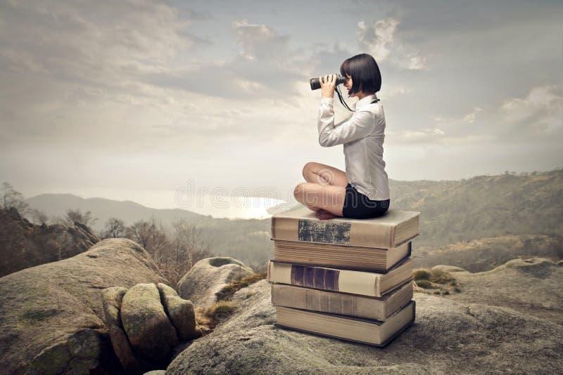 Femme s'asseyant sur une pile des livres photo stock