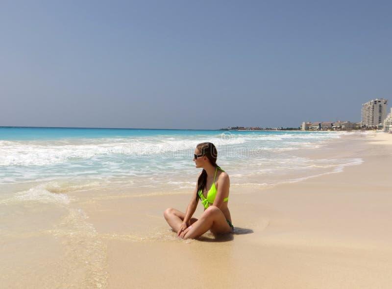Femme s'asseyant sur une plage photo stock