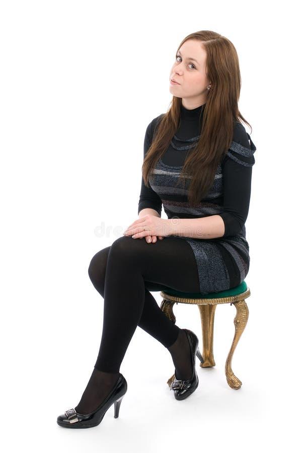 Femme s'asseyant sur une présidence images stock