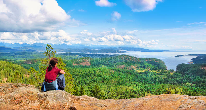 Femme s'asseyant sur une roche et appréciant la belle vue sur l'île de Vancouver, Colombie-Britannique, Canada photos stock