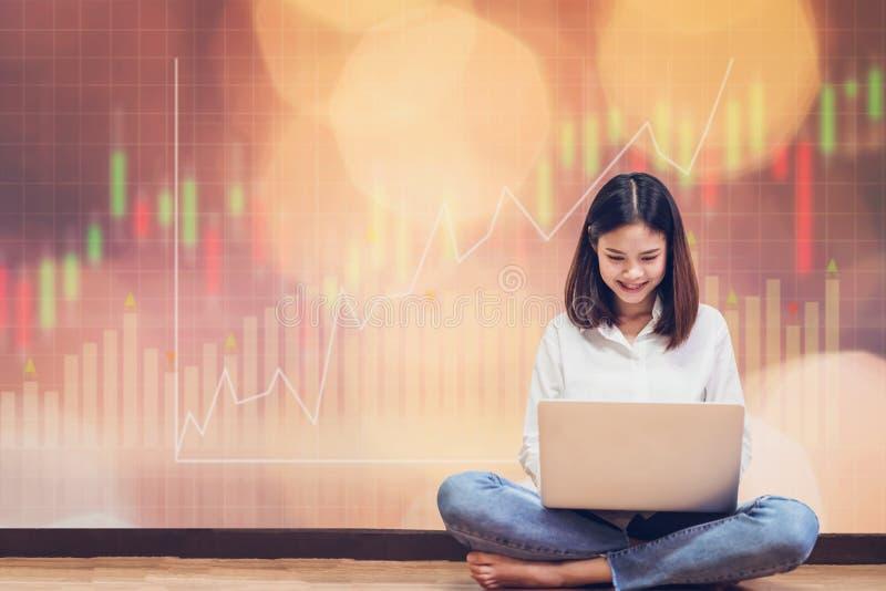 Femme s'asseyant utilisant l'ordinateur portable et le graphique marchand d'exposition avec le graphique de commerce de bourse de photos stock