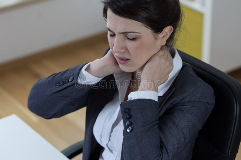 Femme s'asseyante avec douleur photographie stock