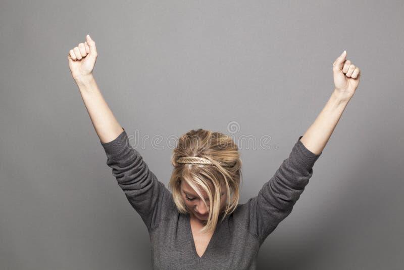 Femme 20s blonde humble soulevant des mains pour la victoire photo stock