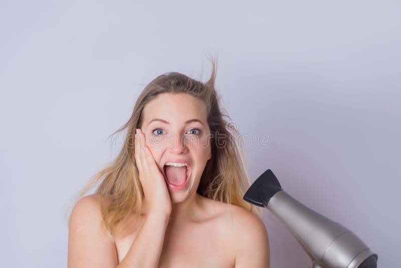 Femme s?chant ses cheveux avec le dessiccateur images libres de droits