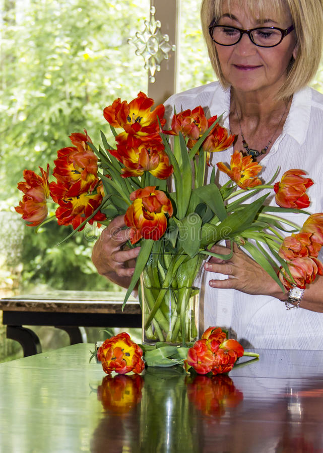 Femme s'chargeant du bouquet des tulipes colorées photo stock