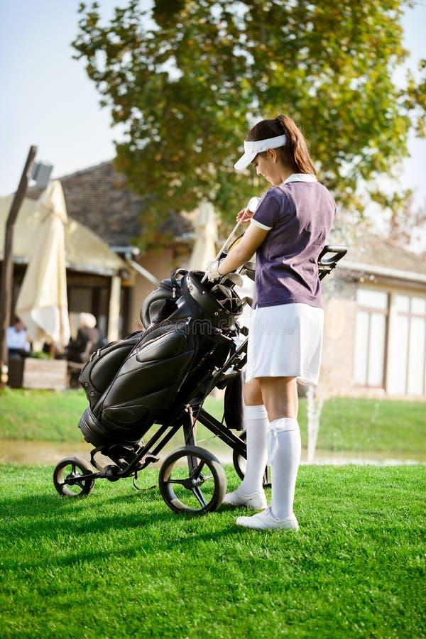 Femme s'chargeant du votre équipement de golf image libre de droits