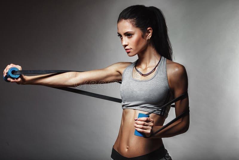 Femme s'exerçant avec la bande en caoutchouc photo stock