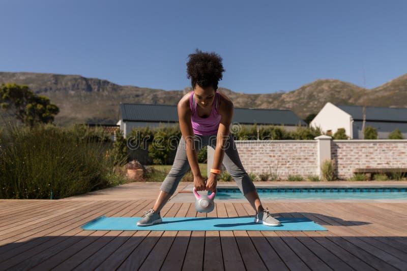 Femme s'exerçant avec le kettlebell dans l'arrière-cour de la maison photos stock