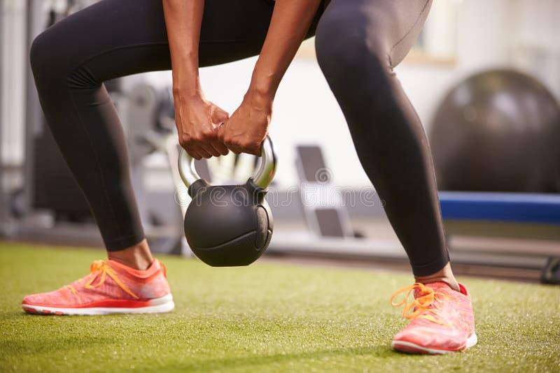 Femme s'exerçant avec un poids de kettlebell, culture de bas-section photographie stock