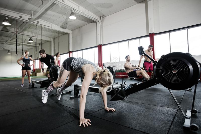 Femme s'exerçant par la machine à ramer dans le gymnase image stock