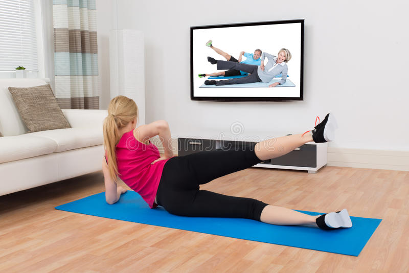 Femme s'exerçant sur l'exercice Mat In Front Of Television images stock