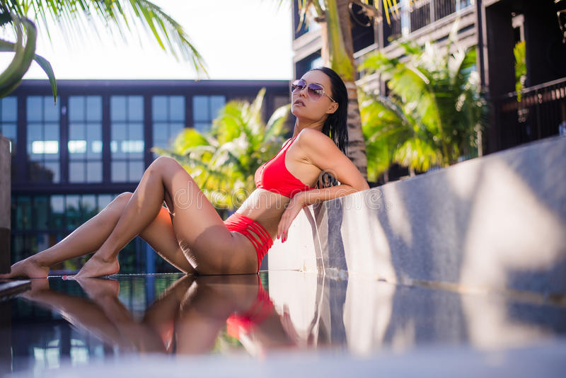 Femme s'exposant au soleil dans le bikini à la ressource tropicale de course Belle jeune femme se trouvant près de la piscine photo stock