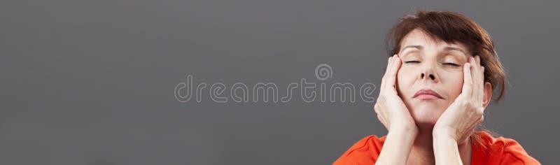 Femme 50s fatiguée détendant pour éviter des bouffées de chaleur, bannière grise photo stock