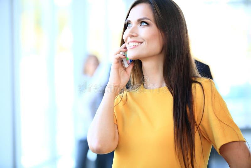 Femme sûre de sourire d'affaires ayant un appel téléphonique photo stock