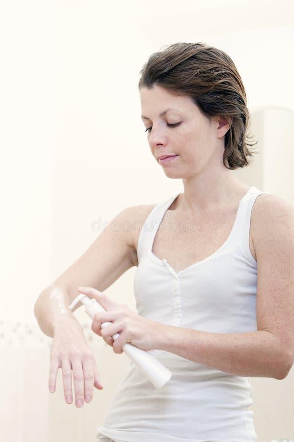 femme 30s s'appliquant hydratant la crème image stock