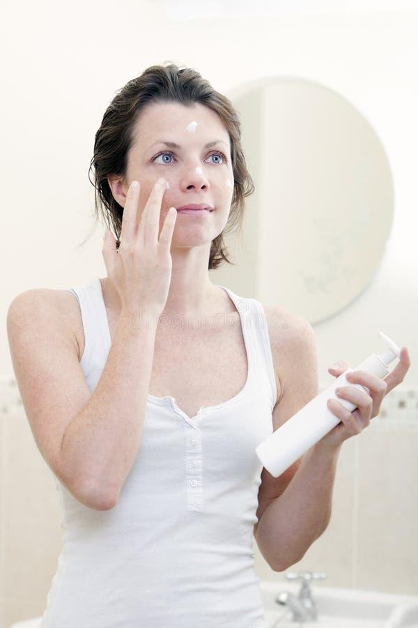 femme 30s s'appliquant hydratant la crème images libres de droits