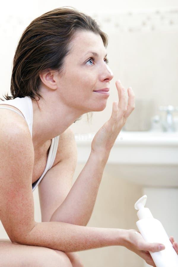 femme 30s s'appliquant hydratant la crème photos stock