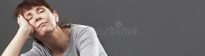 Femme 50s sereine appréciant le petit somme se trouvant sur des coussins, bannière grise photo stock