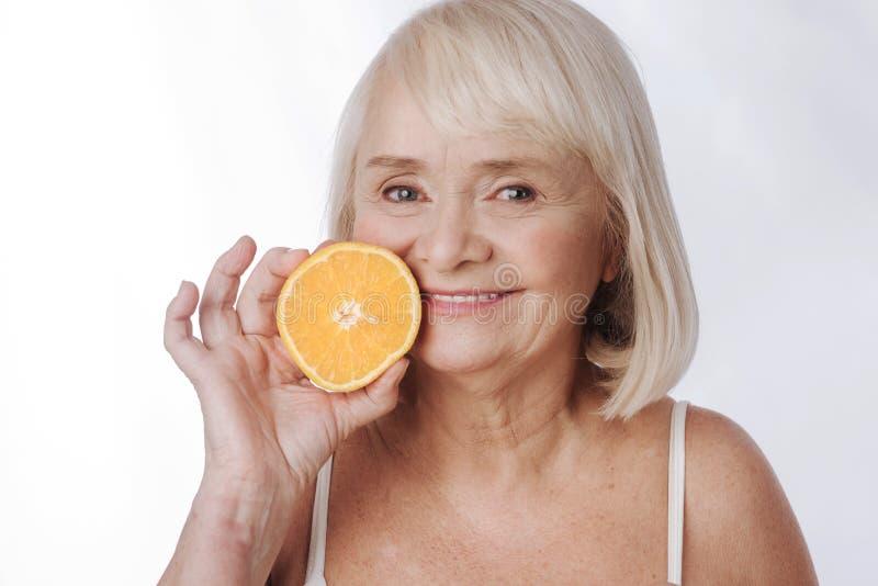 Femme satisfaite agréable tenant une moitié orange image stock