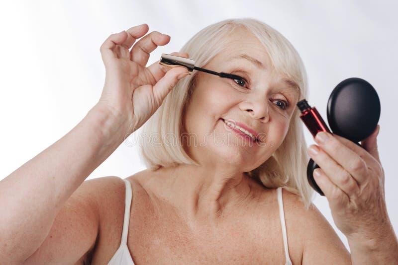 Femme satisfaite belle appliquant le mascara images libres de droits