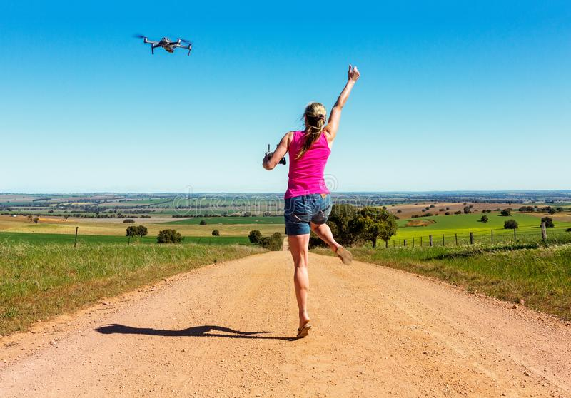 Femme sautant pour la joie le long du chemin de terre pilotant un bourdon images stock