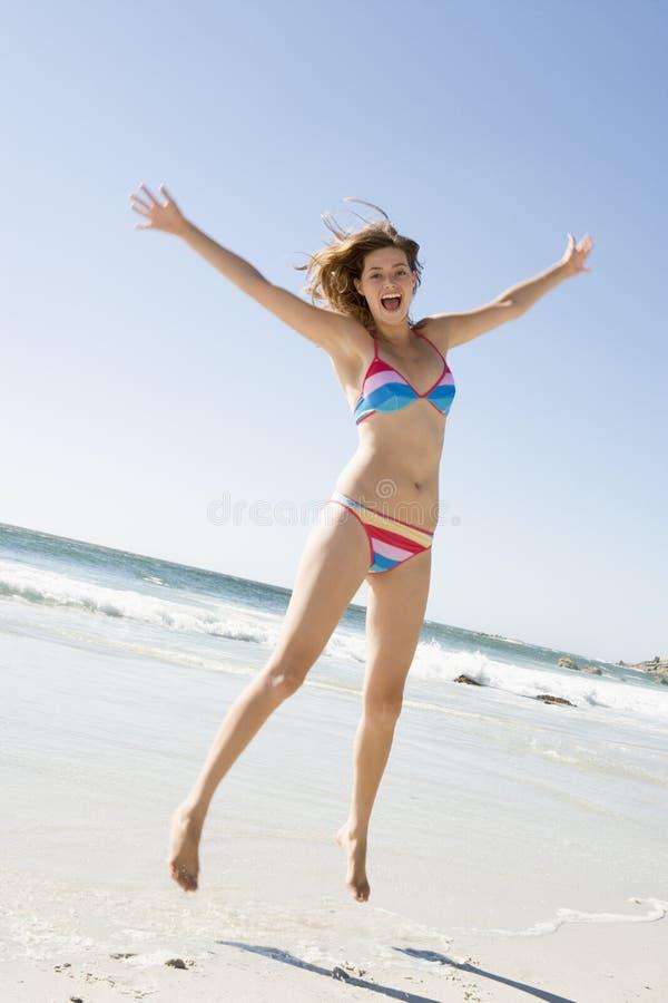 Femme sautant sur la plage image stock