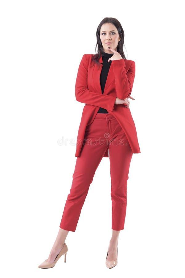 Femme sceptique d'affaires dans le costume rouge avec le doigt sur le menton jugeant et analysant images stock