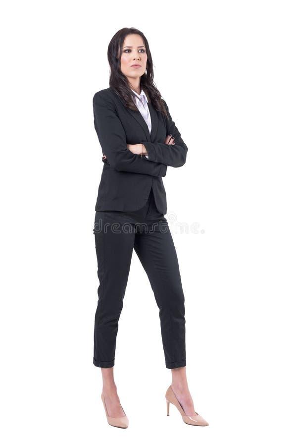 Femme sceptique sérieuse d'affaires avec les bras croisés dans les costumes noirs élégants regardant loin photos libres de droits