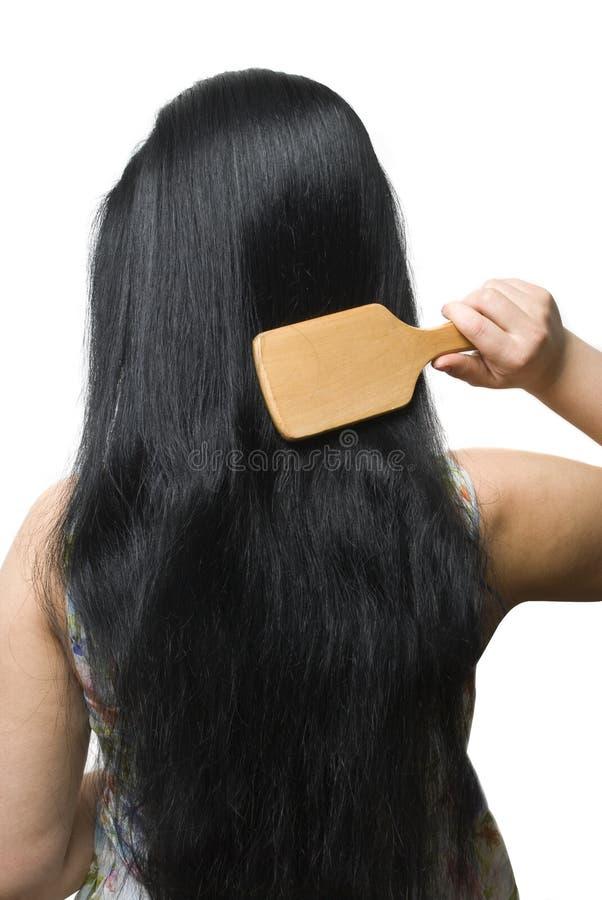 Femme se brossant le long cheveu noir image stock
