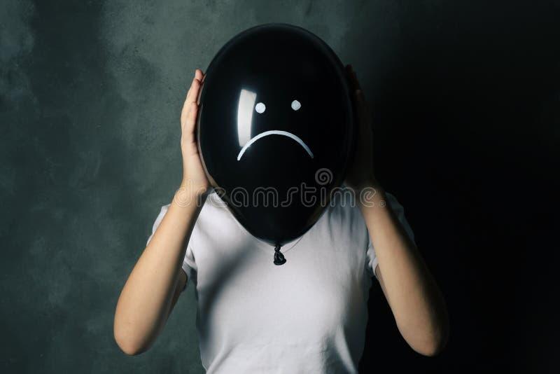 Femme se cachant derrière le ballon noir avec le visage triste tiré sur le fond foncé photos libres de droits