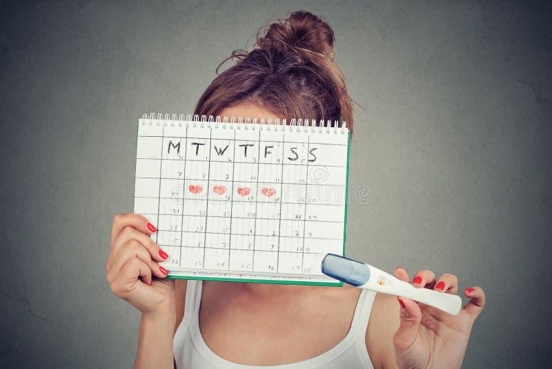 Femme se cachant derrière un calendrier de périodes et montrant un essai de grossesse positif photographie stock libre de droits
