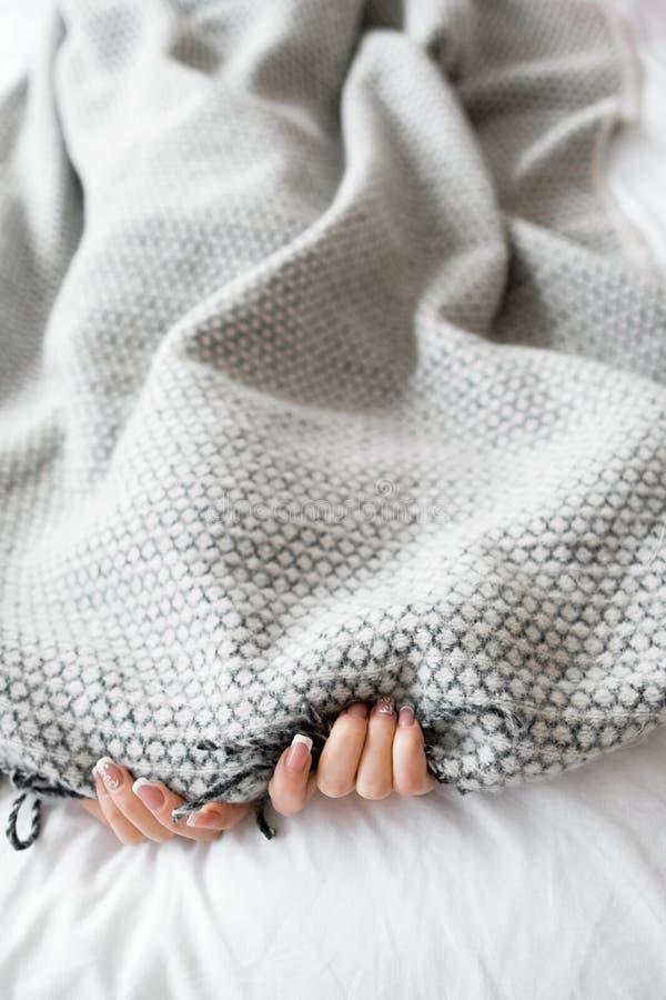 Femme se cachant des problèmes sous la couverture grise photos stock