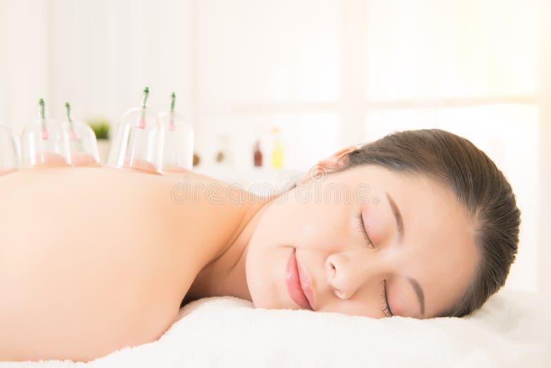 Femme se couchant sur le lit dans le salon de station thermale images libres de droits