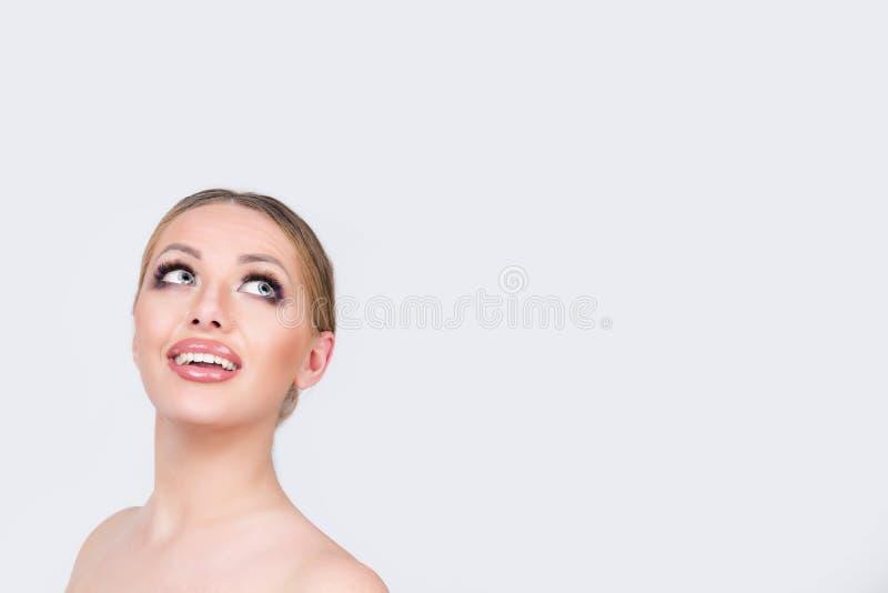 Femme se demandante regardant loin dans le studio photo stock