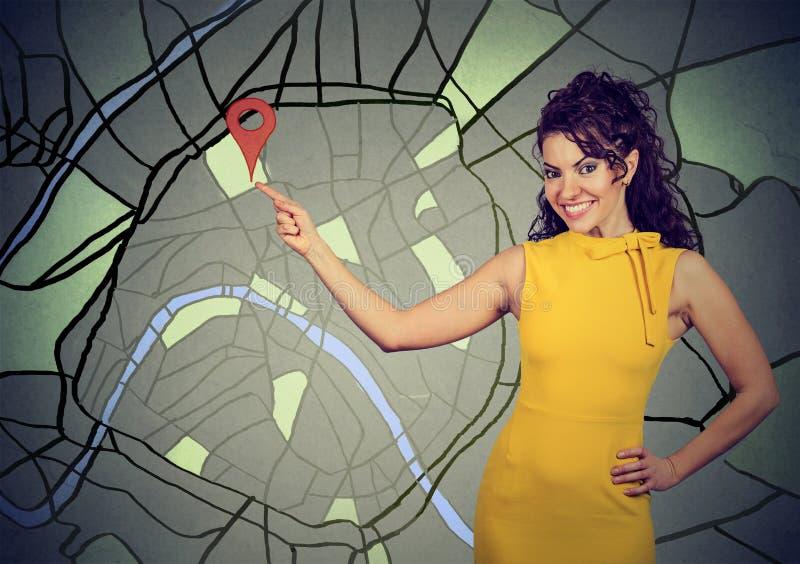 Femme se dirigeant sur la carte montrant l'emplacement photographie stock libre de droits