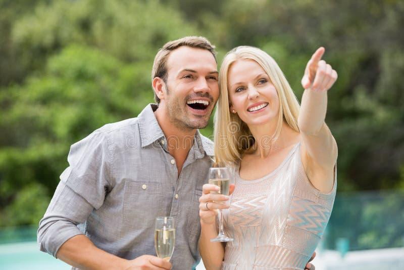 Femme se dirigeant tout en se tenant prêt l'homme tenant la cannelure de champagne photographie stock