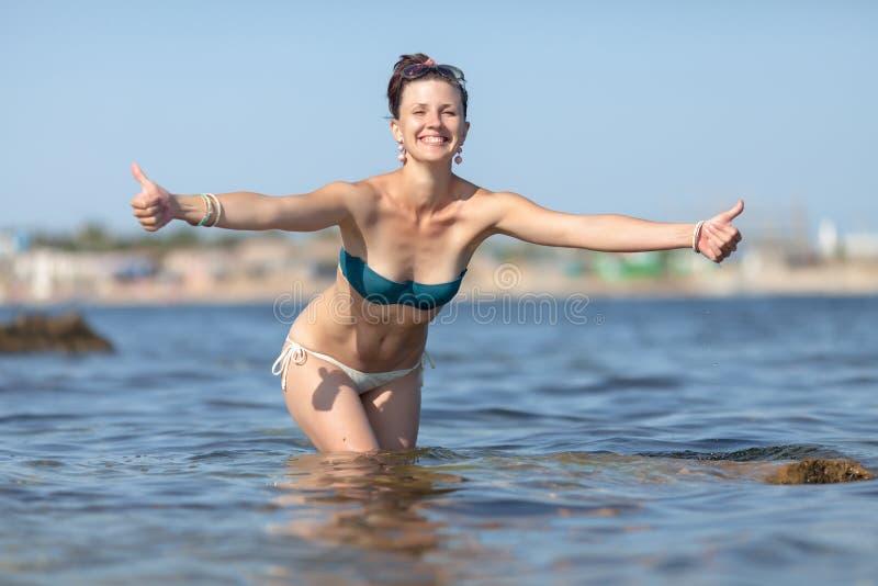 Femme se levant genou-profonde dans la mer et des pouces d'expositions images stock