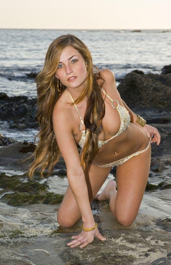Femme se mettant à genoux sur des roches dans un bikini images libres de droits