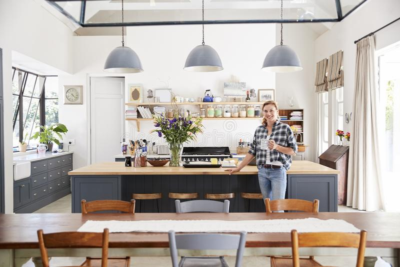 Femme se penchant sur l'île dans une salle à manger de cuisine ouverte de plan photos libres de droits