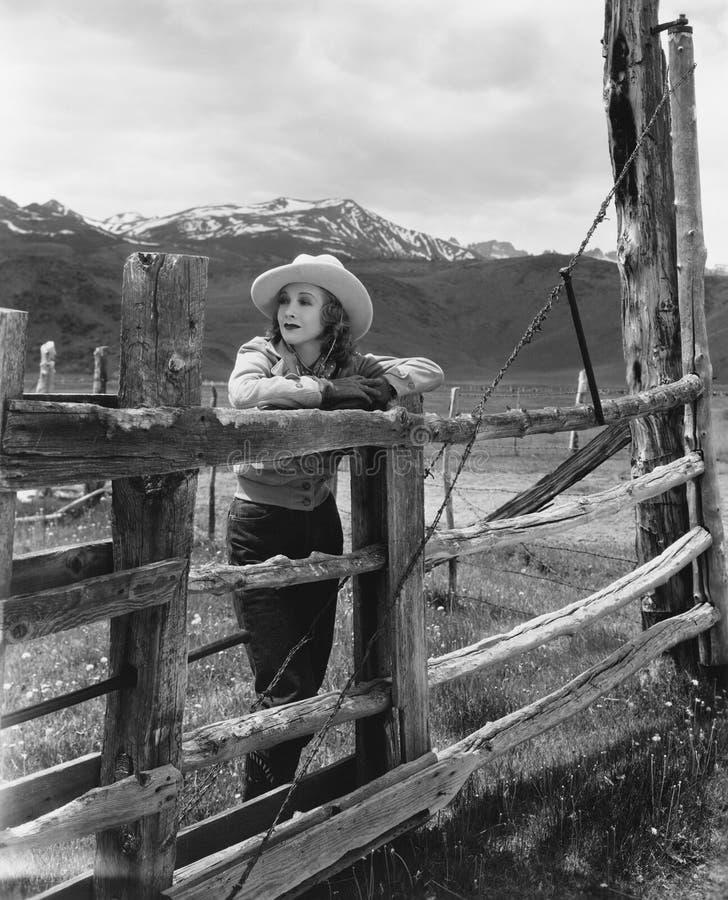 Femme se penchant sur la barrière en bois sur le ranch photos stock