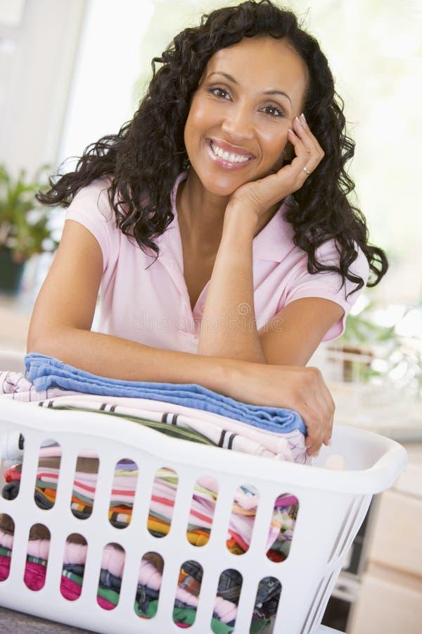 Femme se penchant sur laver dans le panier photo stock
